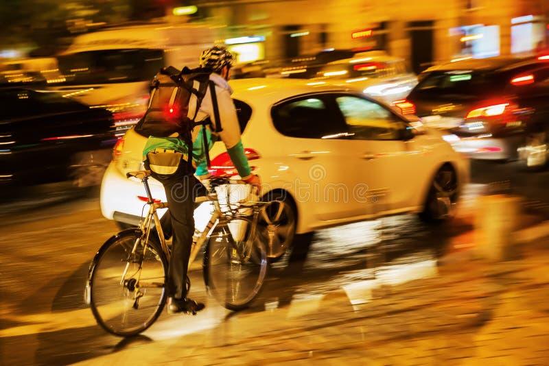 Rowerowy goniec w miasto ruchu drogowym przy nocą obraz royalty free