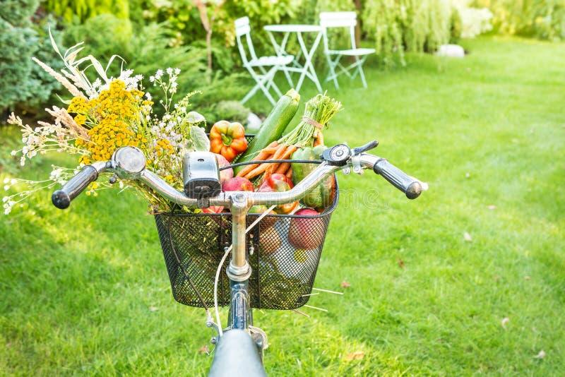 Rowerowy kosz wypełniający z świeżymi warzywami i kwiatami obraz stock