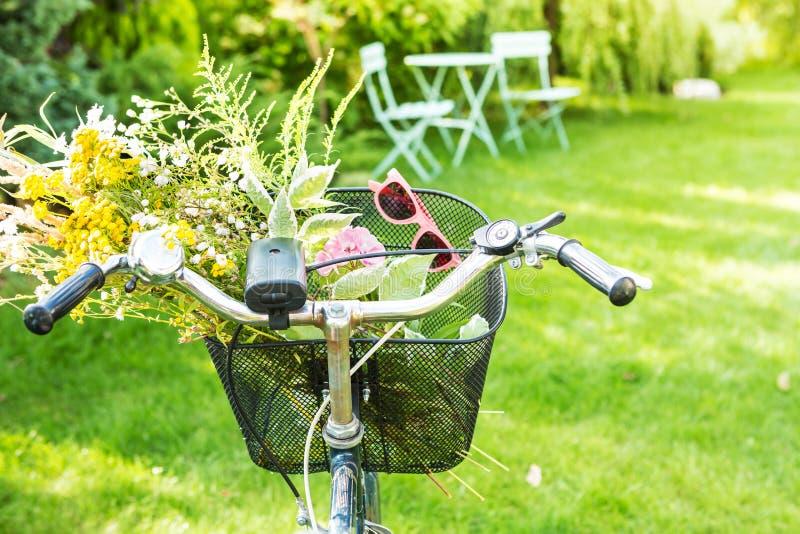 Rowerowy kosz wypełniający z romantyczną kwiat wiązką obrazy stock