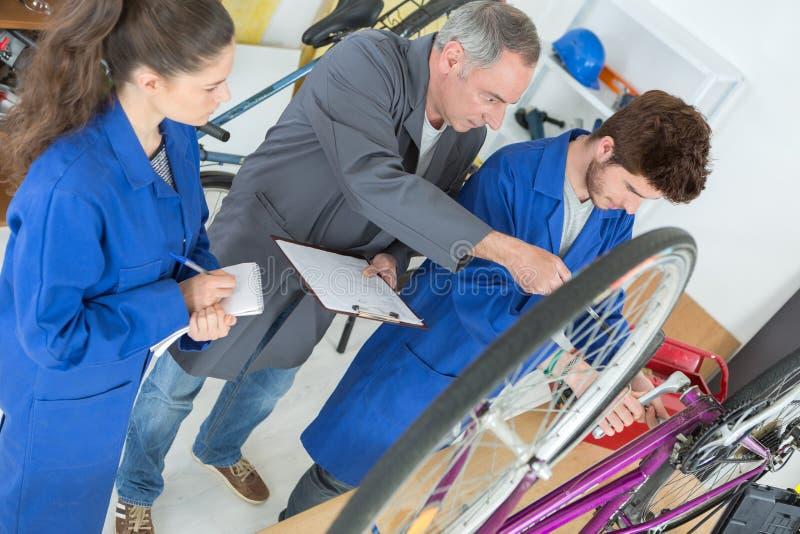 Rowerowy mechanik i aplikanci naprawia rower w warsztacie zdjęcia royalty free