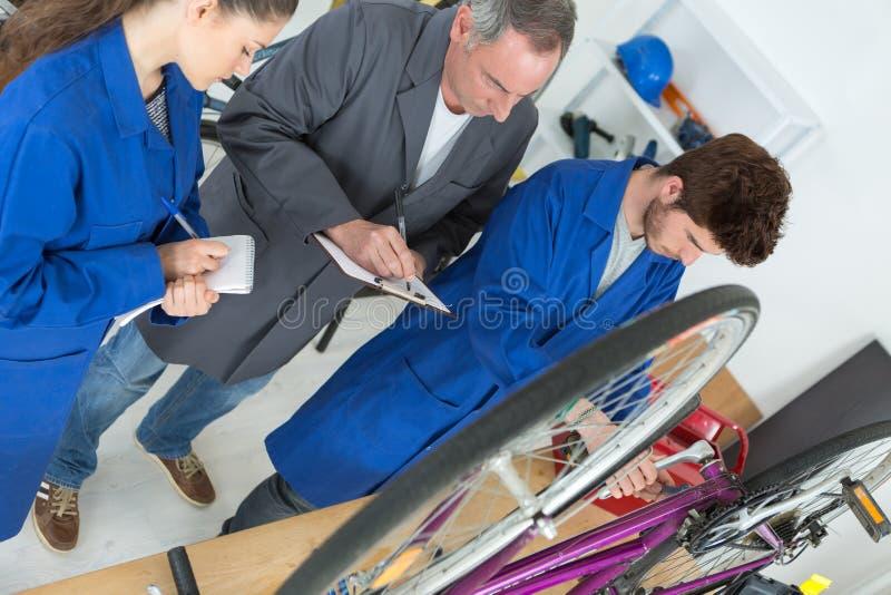 Rowerowy mechanik i aplikanci naprawia rower w warsztacie obrazy stock