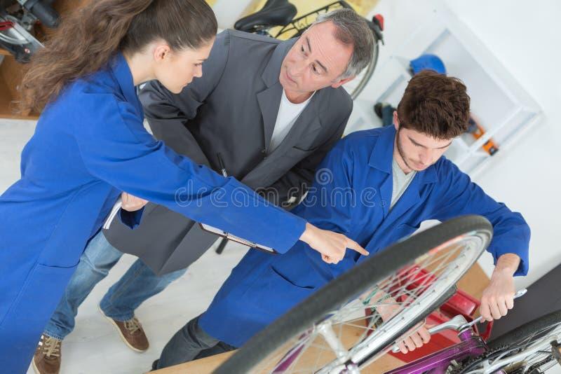 Rowerowy mechanik i aplikanci naprawia rower w warsztacie zdjęcie royalty free