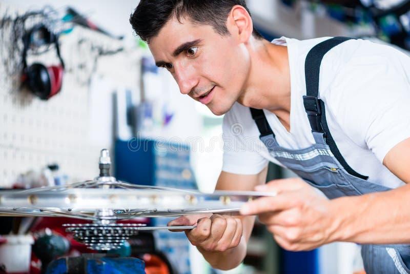 Rowerowy mechanik pracuje w jego roweru warsztacie obraz royalty free