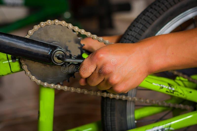 Rowerowy mechanik przystosowywa rowerowego następ w warsztacie w remontowym procesie w zamazanym tle, obraz royalty free