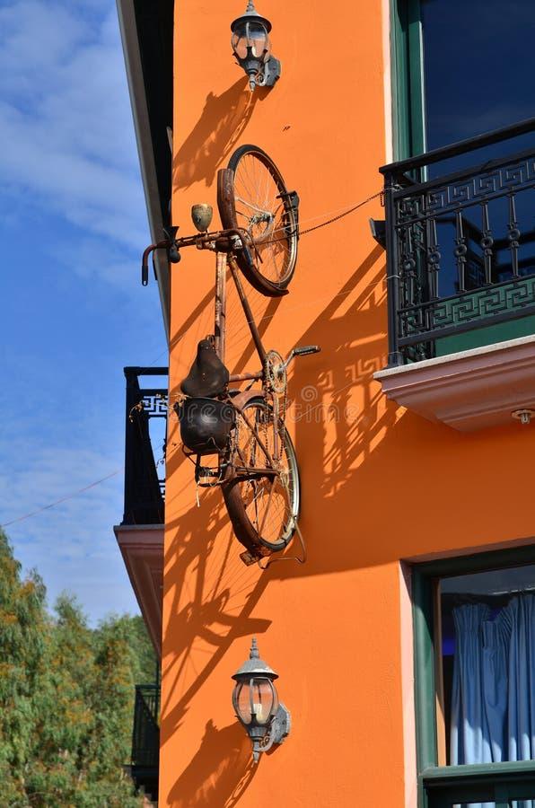 Rowerowy obwieszenie na pomarańczowej ścianie obrazy stock