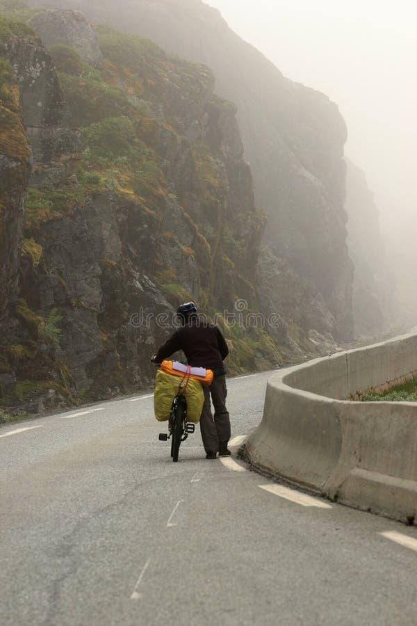 Rowerowy turysta pcha jego rower w górę halnej drogi w mgłowej pogodzie zdjęcie royalty free