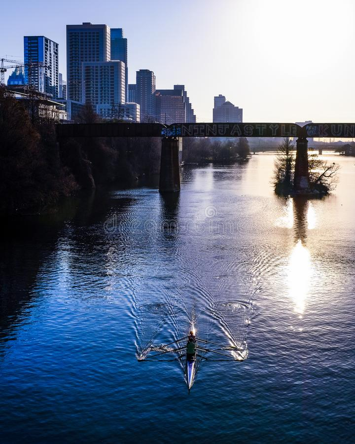 Rowing in Town Lake in the Morning Sunlight. Rowers on Town Lake in the city of Austin, Texas as the sun rises on a summer day royalty free stock photos
