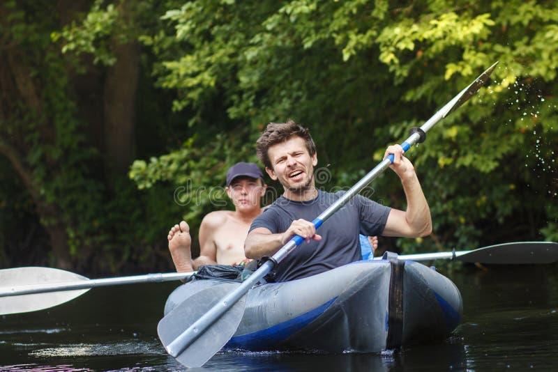 Rowers w łódkowatym żaglu wzdłuż rzeki i rzędu wioseł na letnim dniu Sporty faceci są flisactwem zestrzelają rzekę leisure Grupa  fotografia royalty free