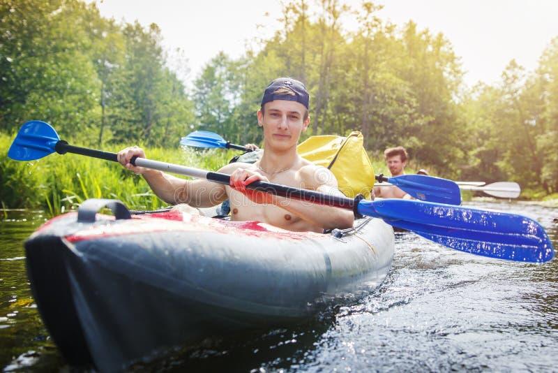 Rowers w kajaku z wiosłami żeglują wzdłuż rzeki na jaskrawym letnim dniu Młodzi sportowi mężczyzna wiosłują wiosła na wodzie w ło fotografia stock