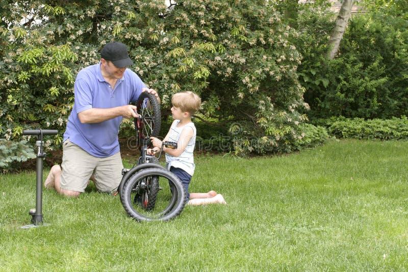 roweru tata naprawiania syn zdjęcie royalty free