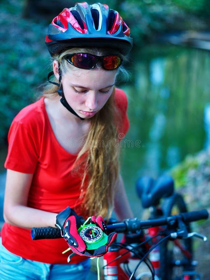Rowery jeździć na rowerze dziewczyny jest ubranym hełma spojrzenie przy kompasem zdjęcia stock