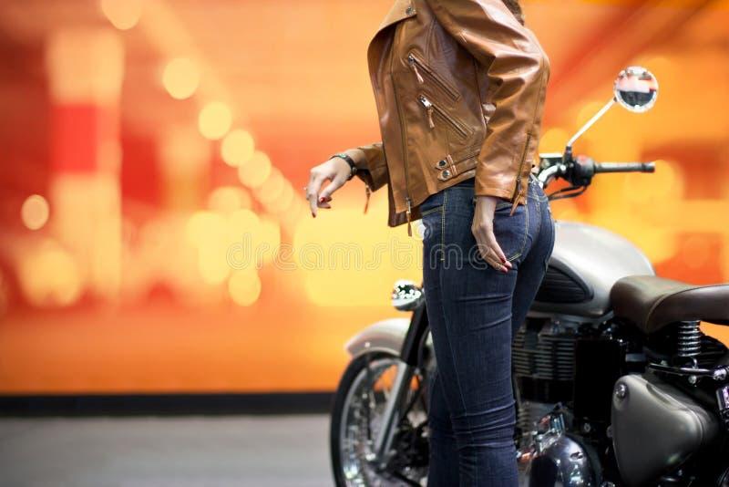 Rowerzysta kobieta w brown skórzanej kurtce z motocyklem zdjęcia stock
