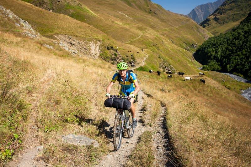 Rowerzysta pcha jego bicykl up w wysokich Kaukaz górach obrazy royalty free