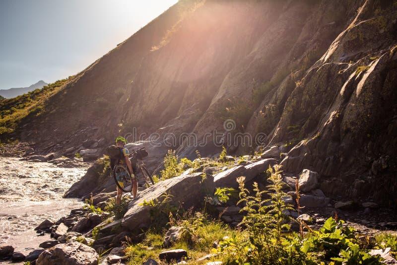 Rowerzysta pcha jego bicykl up w wysokich Kaukaz górach obraz royalty free