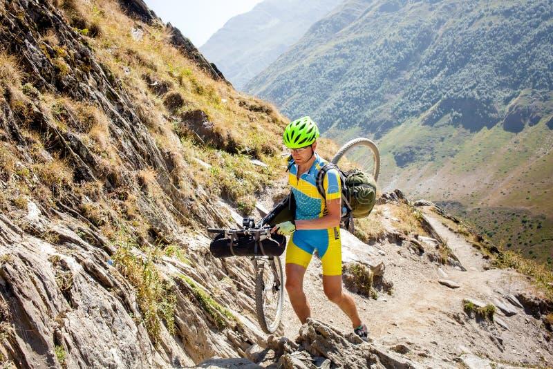 Rowerzysta pcha jego bicykl up w wysokich Kaukaz górach obrazy stock