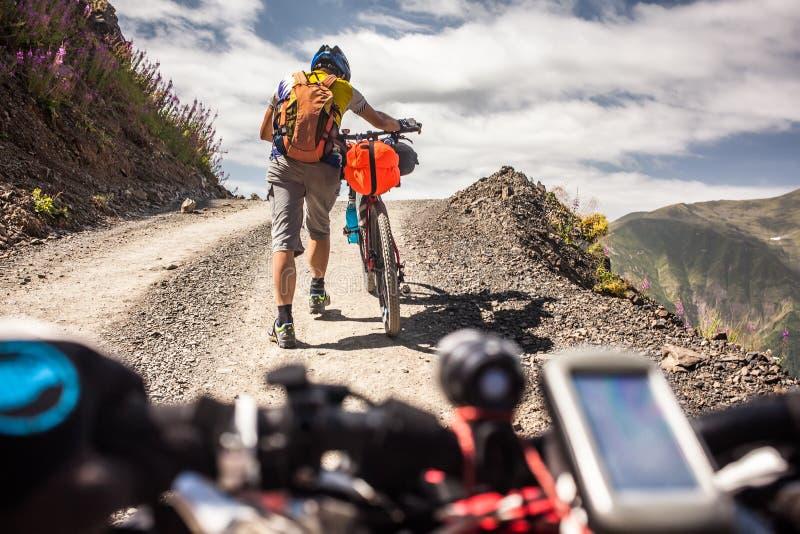 Rowerzysta pcha jego bicykl up w wysokich Kaukaz górach fotografia royalty free