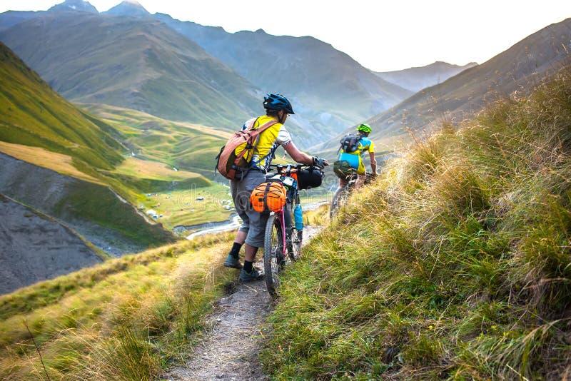 Rowerzysta pcha jego bicykl up w wysokich Kaukaz górach zdjęcie stock