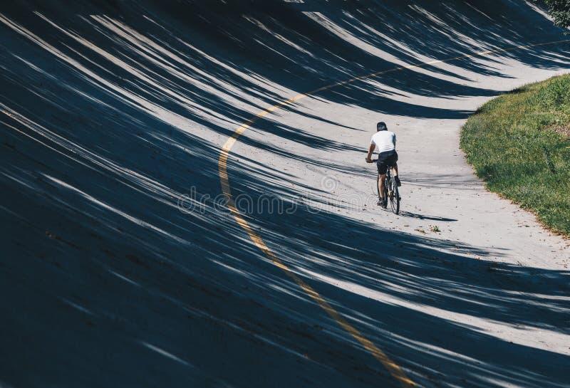 Rowerzysta z rowerem górskim wzdłuż ścieżki w starym tor wyścigów konnych żużel przypowieściowy w Autodrome Monza, Lombardy, Włoc fotografia royalty free