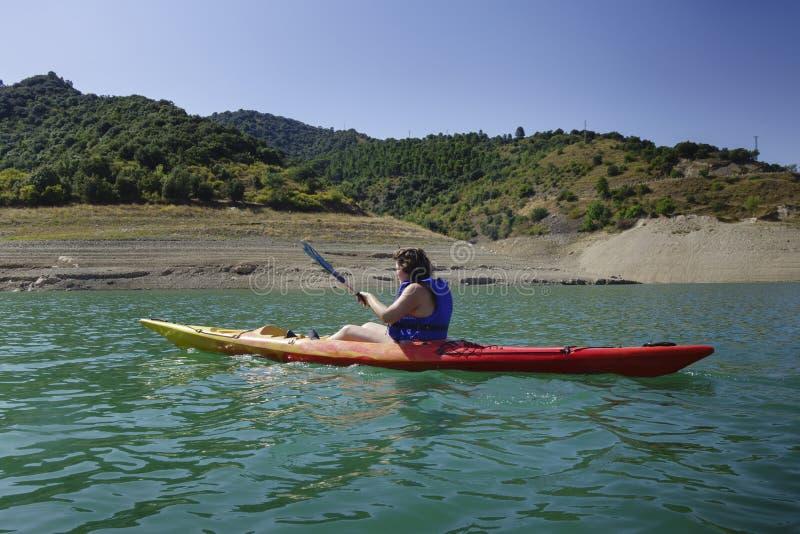 Rowing молодой женщины в каяке стоковые фотографии rf