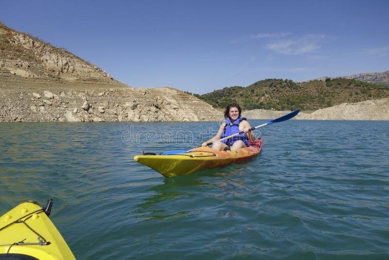Rowing молодой женщины в каяке стоковое фото rf