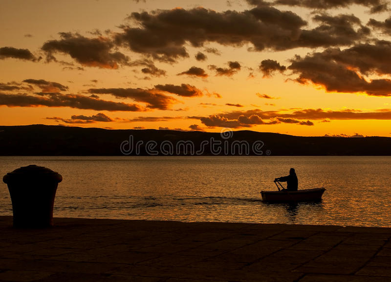 Rowing alone in sunset royalty free stock images