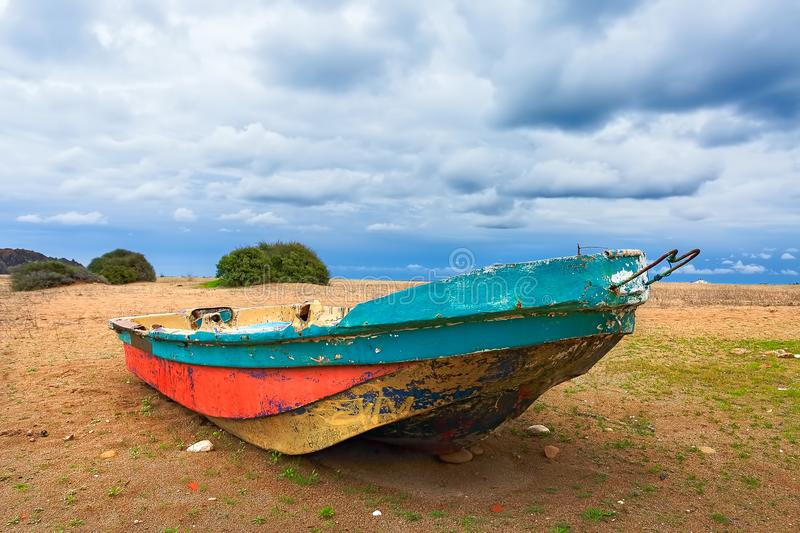 A rowing boat on the beach. Flat-bottomed boat on the sandy shore of the beach. Sunset on the beach. Sparse vegetation royalty free stock photography