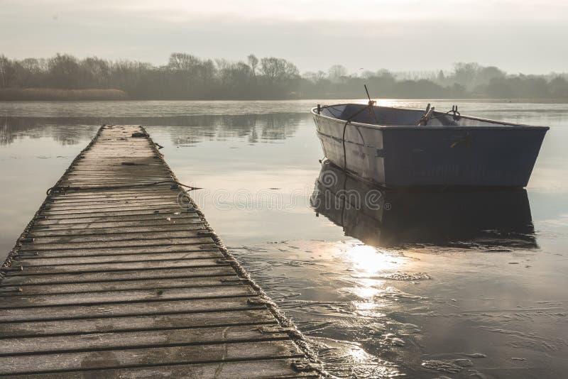 A rowing boat floats adrift on a frozen lake beside an empty walkway royalty free stock image