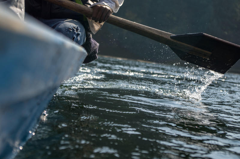 The rowing of boat. A man rowing a boat in a lake royalty free stock images