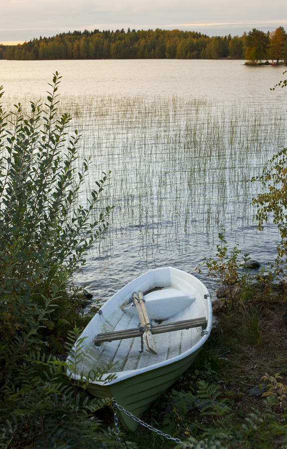 Rowing boat moored by lake stock photo