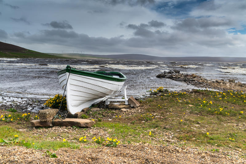 Rowing boat on shore of a stormy Scottish Loch, Orkney UK. Green and white rowing boat on shore of a stormy Scottish Loch, Orkney UK royalty free stock image