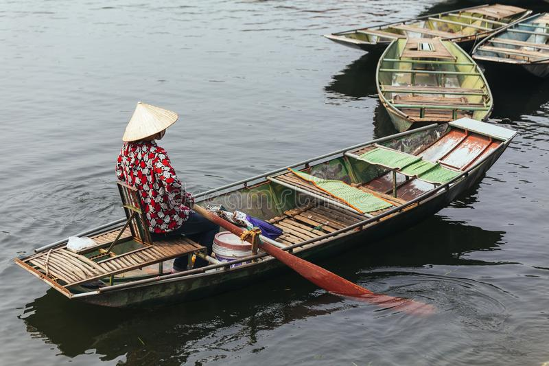 Rowing boat woman wearing red and white colors shirt, conical hat and mouth mask sitting in a boat with paddles over the river. royalty free stock photo