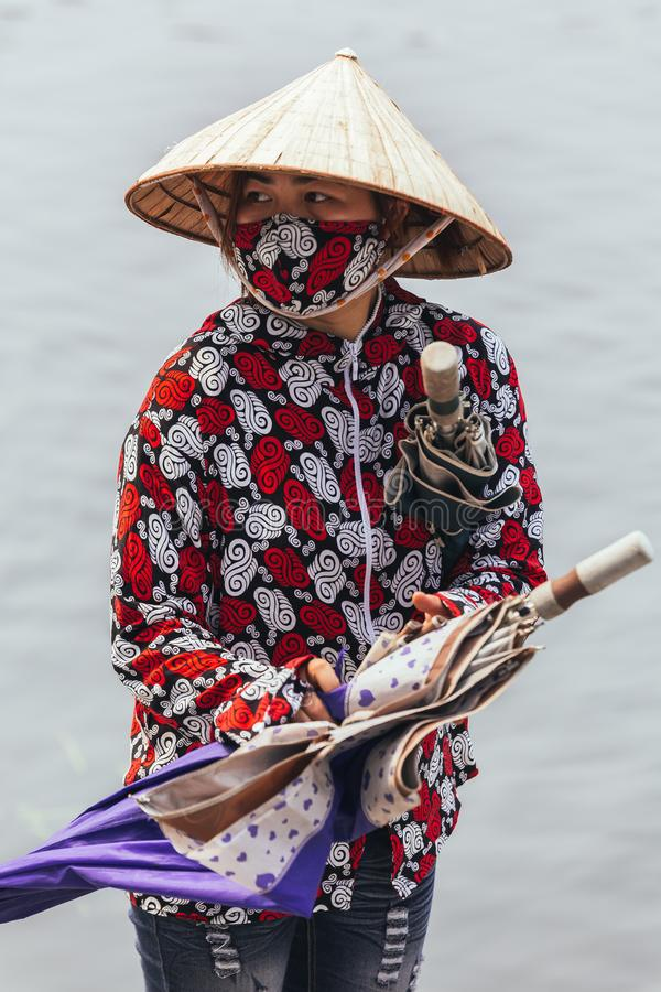 Rowing boat woman wearing red and white colors shirt, conical hat and mouth mask stand and carry umbrellas in Ninh Binh, Vietnam stock images