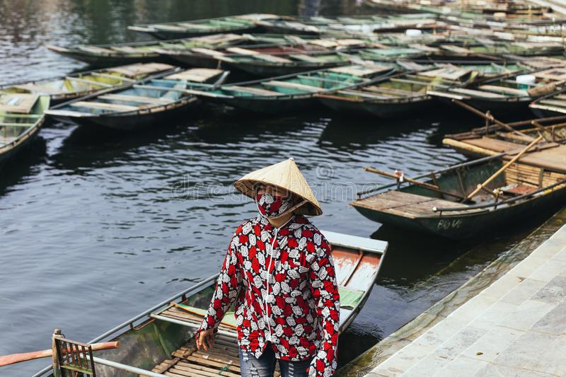 Rowing boat woman wearing red and white colors shirt, conical hat and mouth mask standing with empty boats over the river. royalty free stock photography