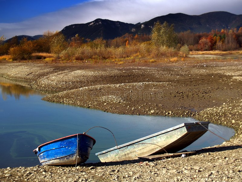 Rowing boats by lake. Two wooden rowing boats moored by lake in countryside with mountain range in background royalty free stock photos