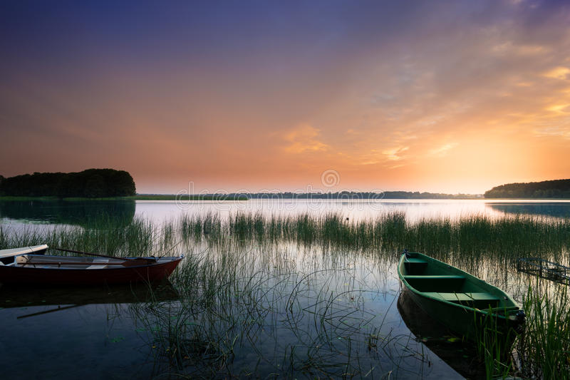 Rowing boats on sunset stock images