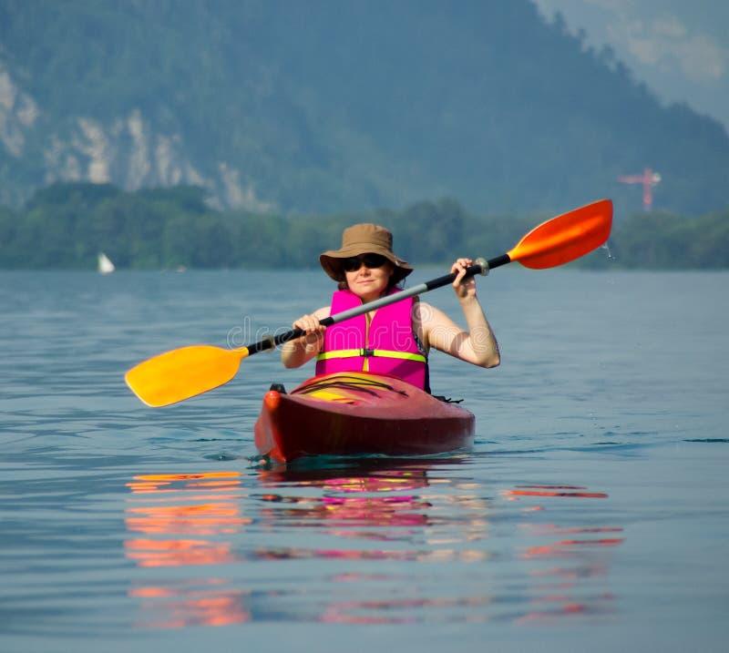 Rowing de la mujer en kajak fotos de archivo
