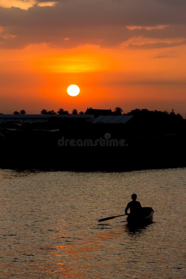Rowing man in boat at sunset. Bangkok, Thailand stock photo