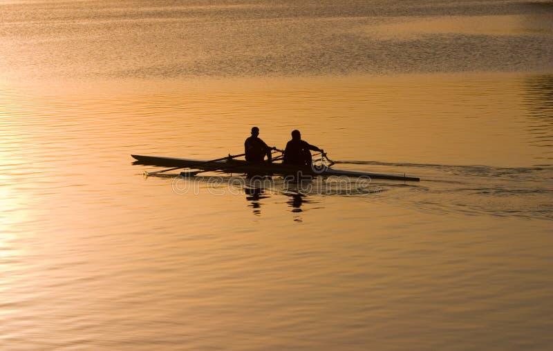 Rowing at sunrise stock image