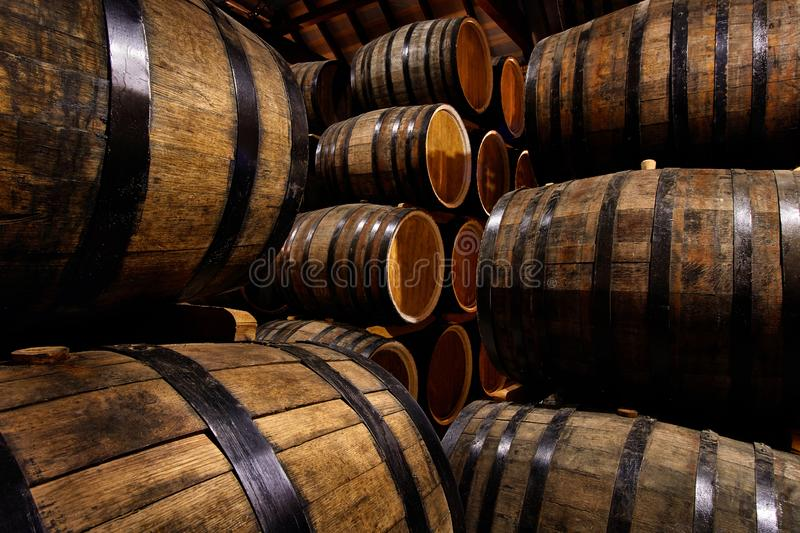 Rows of alcoholic drums in stock. Distillery. Cognac, whiskey, wine, brandy. Alcohol in barrels. Rows of alcoholic drums in stock. Distillery. Cognac, whiskey royalty free stock photo