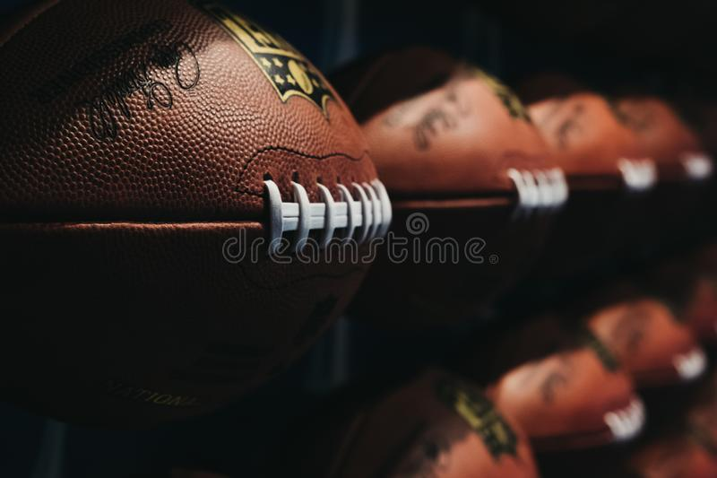Rows of american football balls in NFL Experience in Times Square, New York, USA. New York, USA - MAY 28, 2018: Rows of american football balls in NFL Experience royalty free stock photos