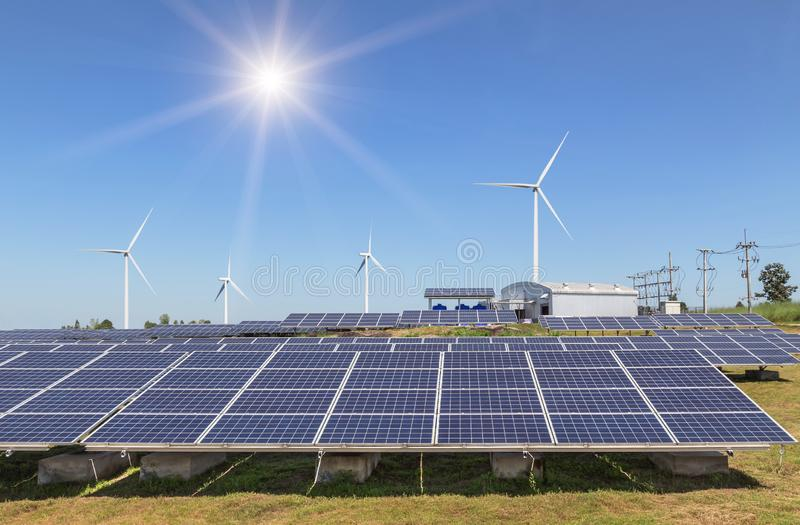 Rows array of polycrystalline silicon solar panels and wind turbines generating electricity in hybrid power plant. Systems station alternative renewable energy royalty free stock photo