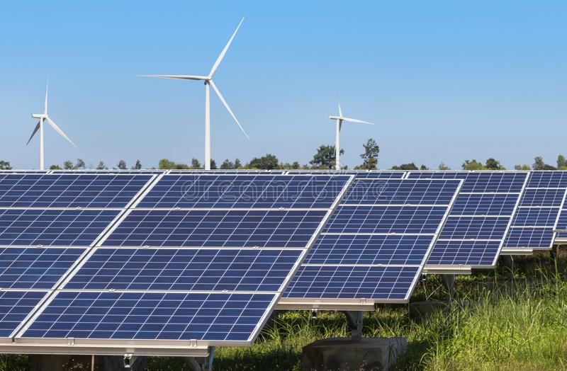 Rows array of polycrystalline silicon solar panels and wind turbines generating electricity in hybrid power plant systems station. Alternative renewable energy stock photo