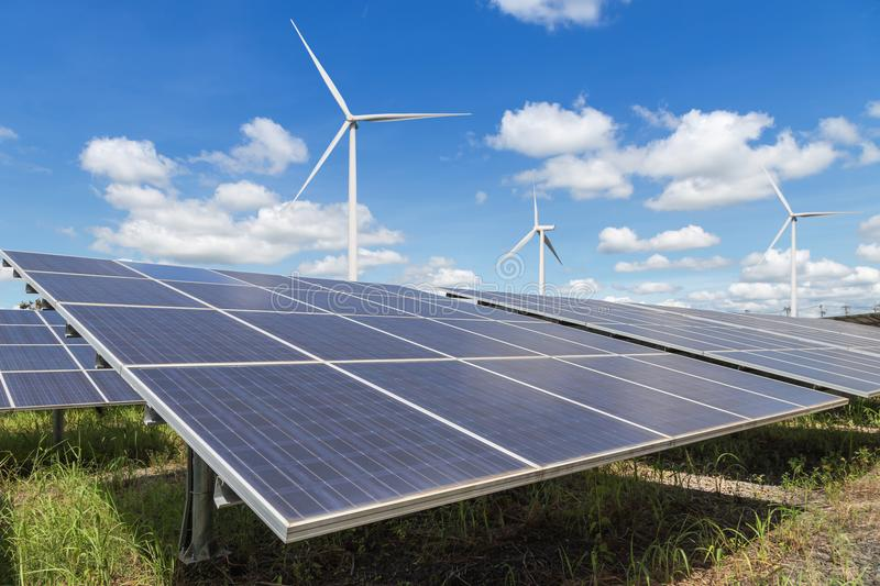 Rows array of polycrystalline silicon solar panels and wind turbines generating electricity in hybrid power plant systems station. Alternative renewable energy stock photos