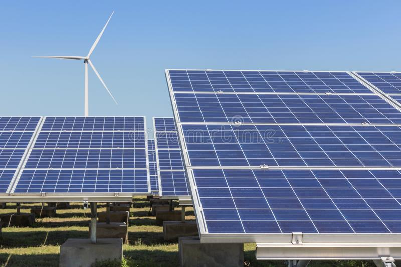 Rows array of polycrystalline silicon solar panels and wind turbines generating electricity in hybrid power plant systems station. Alternative renewable energy royalty free stock photos
