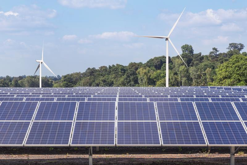 Rows array of polycrystalline silicon solar panels and wind turbines generating electricity in hybrid power plant systems station. Alternative renewable energy stock image