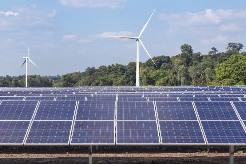 Rows array of polycrystalline silicon solar panels and wind turbines generating electricity in hybrid power plant systems station. Alternative renewable energy royalty free stock photo