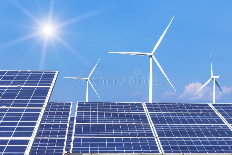 Rows array of polycrystalline silicon solar panels and wind turbines generating electricity in hybrid power plant systems station. Alternative renewable energy stock images