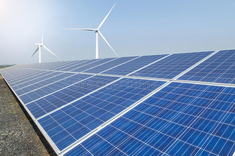Rows array of polycrystalline silicon solar panels and wind turbines generating electricity in hybrid power plant systems station. Alternative renewable energy royalty free stock photography