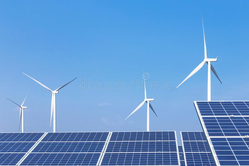 Rows array of polycrystalline silicon solar panels and wind turbines generating electricity in hybrid power plant systems station. Alternative renewable energy stock photography