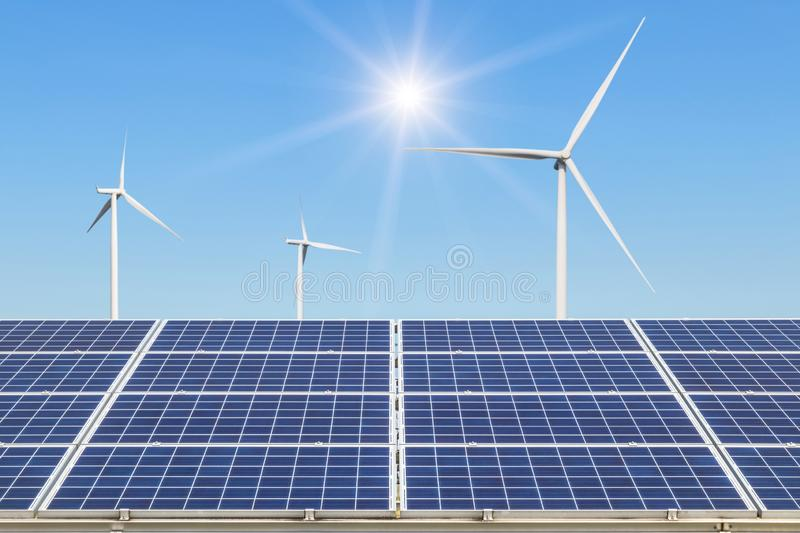 Rows array of polycrystalline silicon solar panels and wind turbines generating electricity in hybrid power plant systems station. Alternative renewable energy royalty free stock images